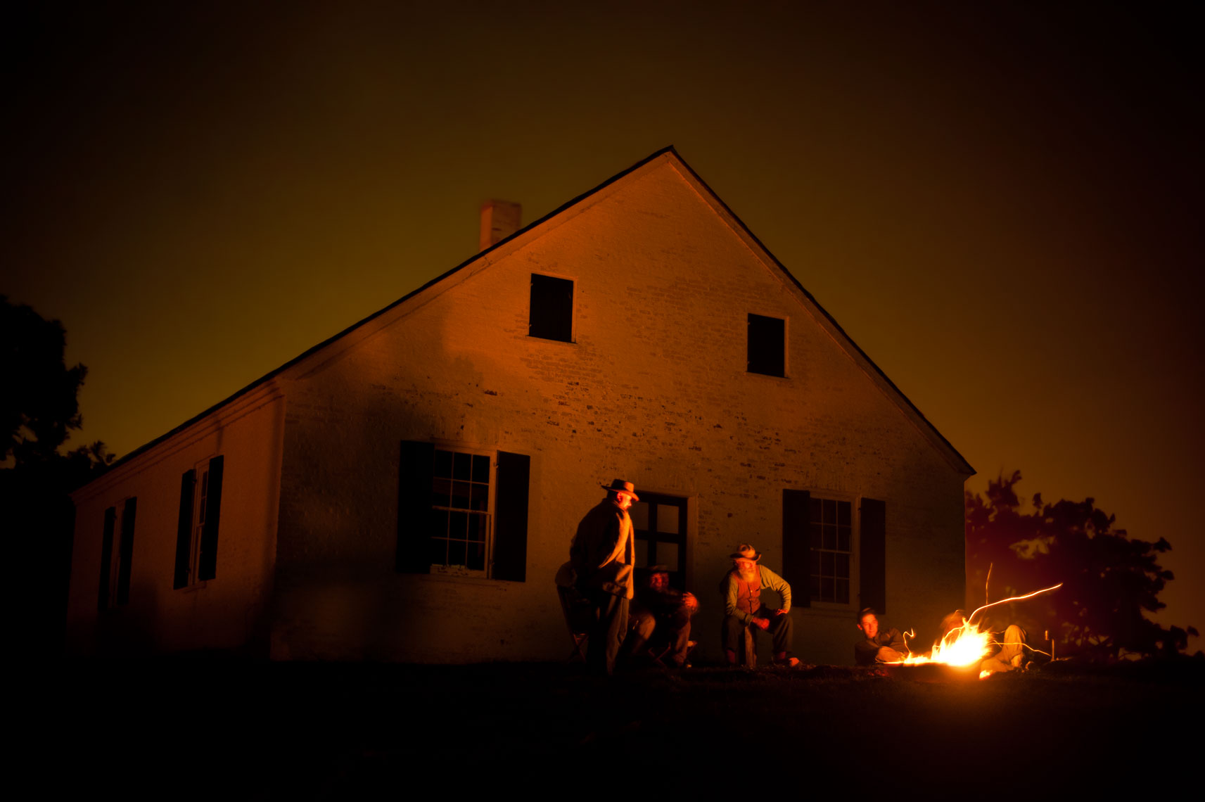 Civil War reenactors at Antietam: men sit around the campfire in front of historic Dunker Church on the battlefield