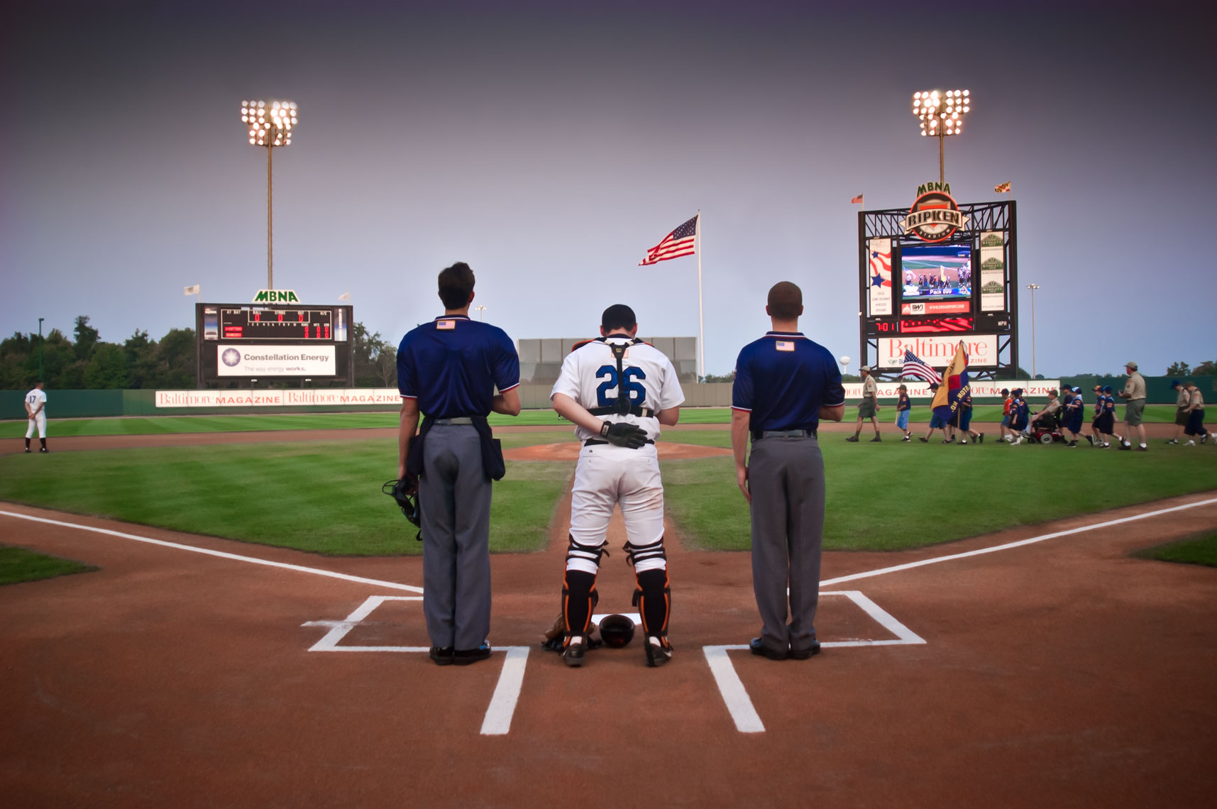 A catcher and umpires stand for the national anthem at the home of the Aberdeen Ironbirds