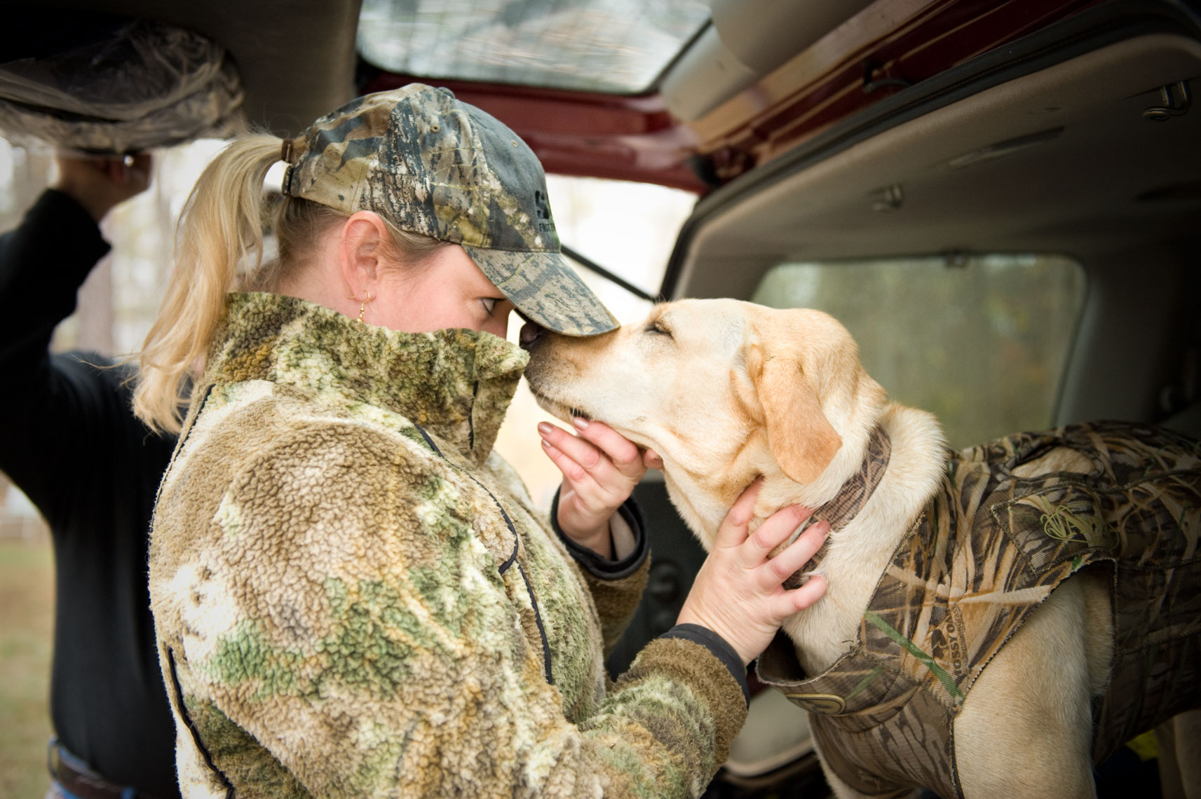 Hunting for waterfowl on the Eastern Shore of Maryland: A female hunter bonds with her dog before the hunt begins