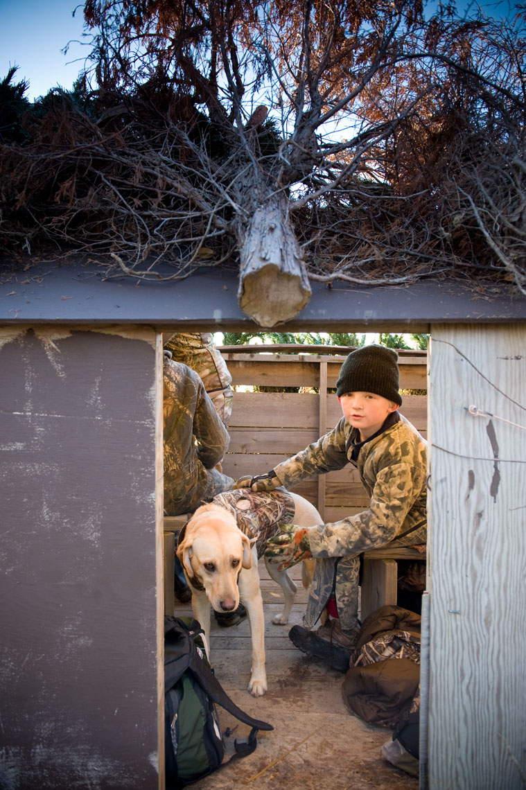 Hunting for waterfowl on the Eastern Shore of Maryland: a young boy waits in the blind with his retriever
