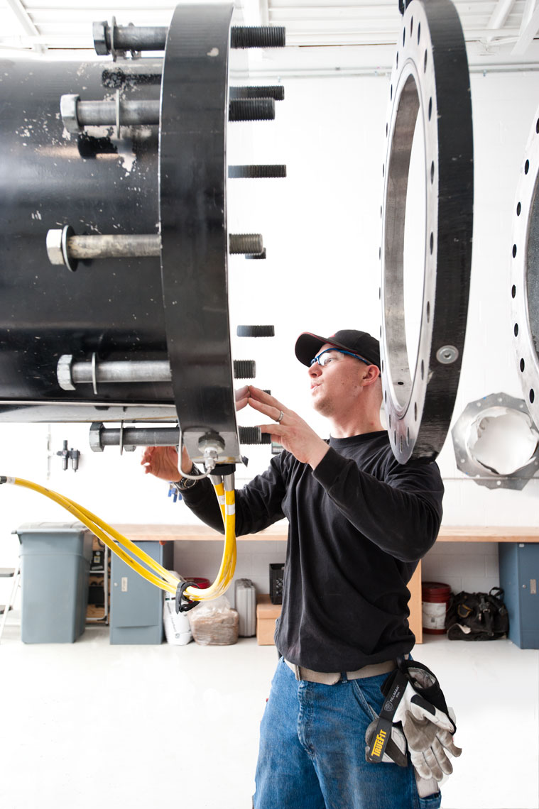 A factory worker wearing a black shirt and hat looking at pipe connections