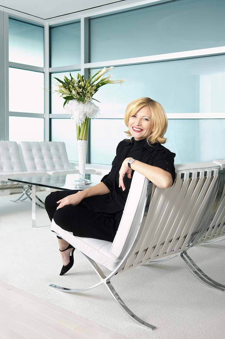 A smiling woman seated in an upscale modern couch