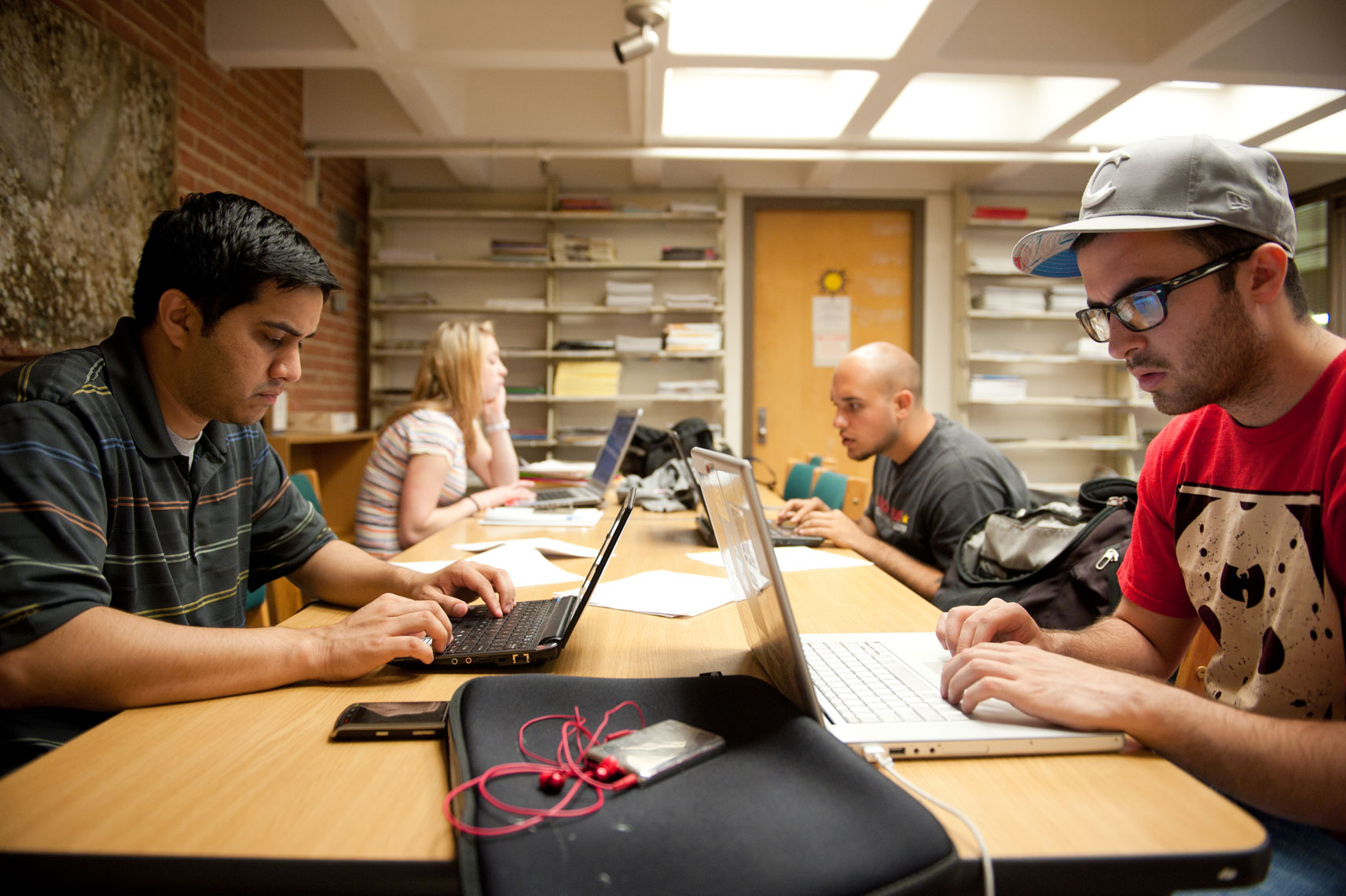 Students working at laptops at a table in the library