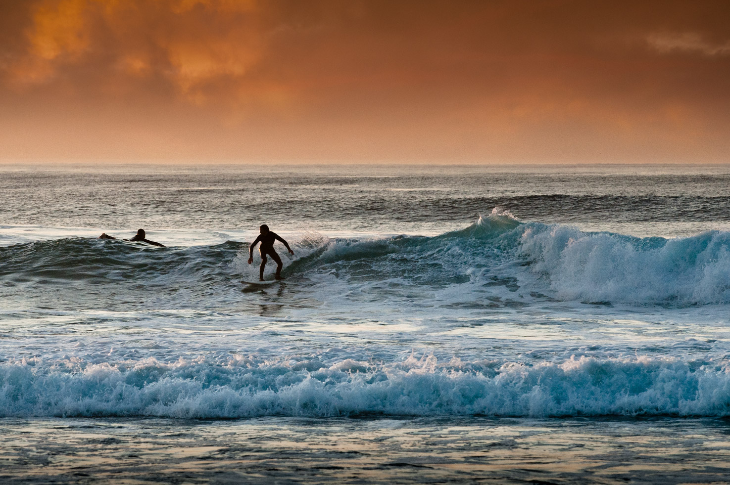 A surfer rides along a wave at sunset at Asilomar State Beach, Pacific Grove, California