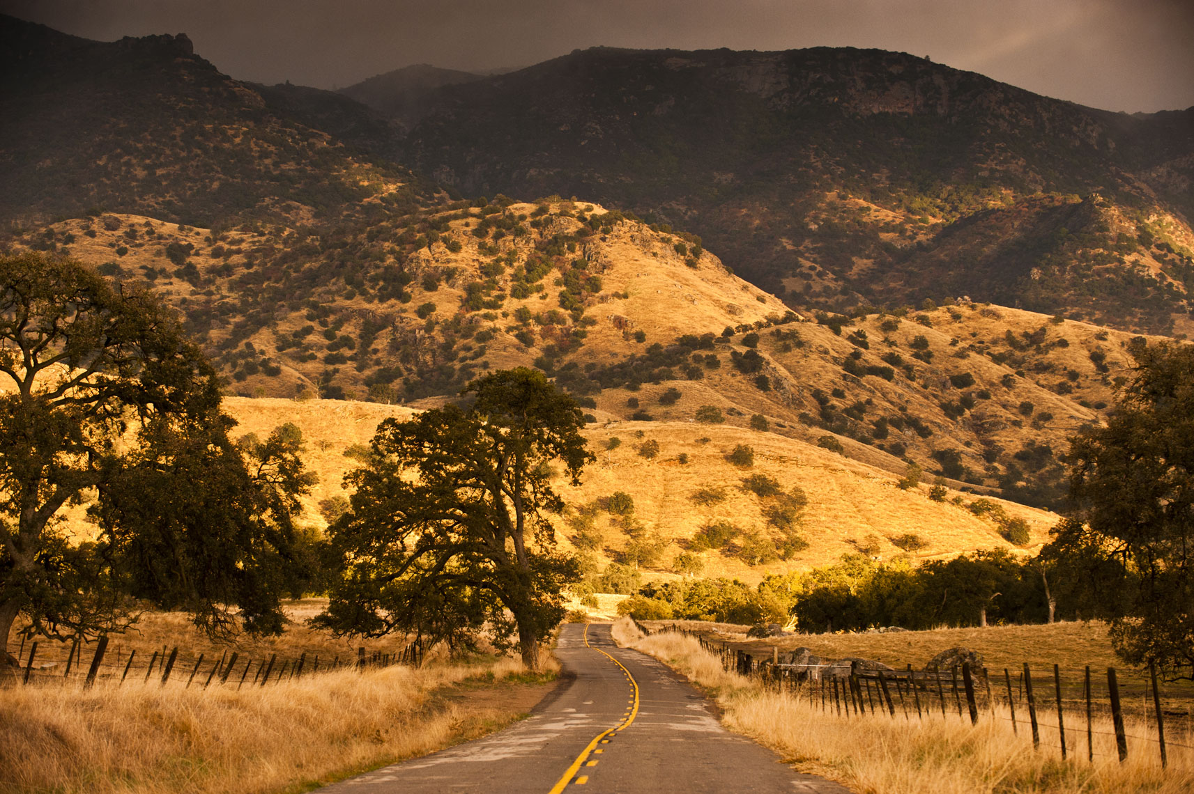 An empty highway leads toward darkening hills in the Yokohl Valley, California
