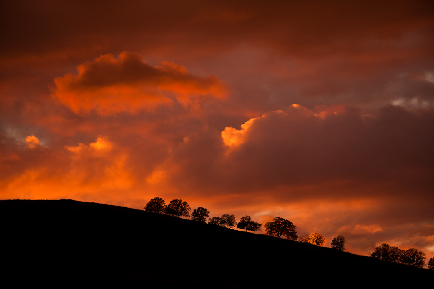 Deep sunset colors in the sky behind a silhouetted hillside in Yokohl Valley, California