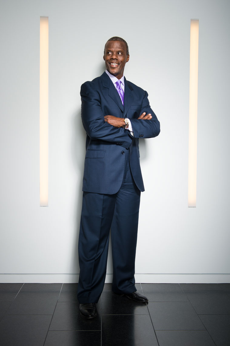 JC Watts smiling with his arms crossed in between two vertical lights