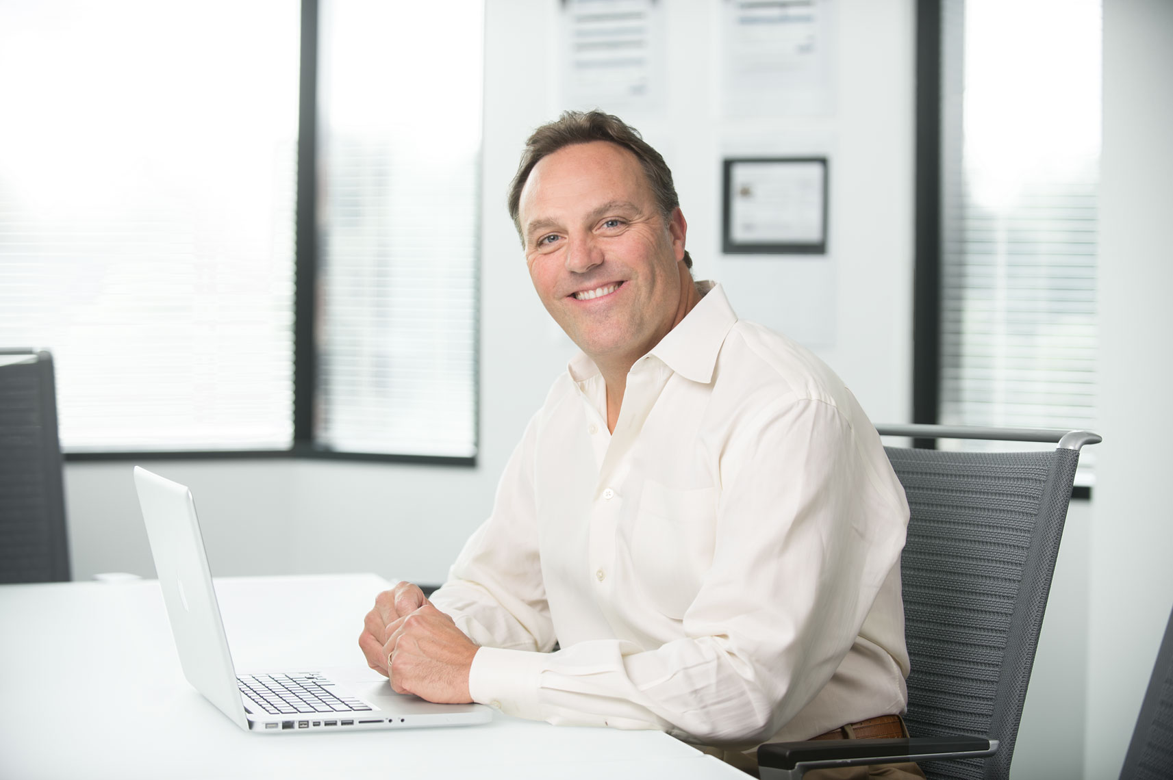 A man smiling with a laptop at a board room conference table