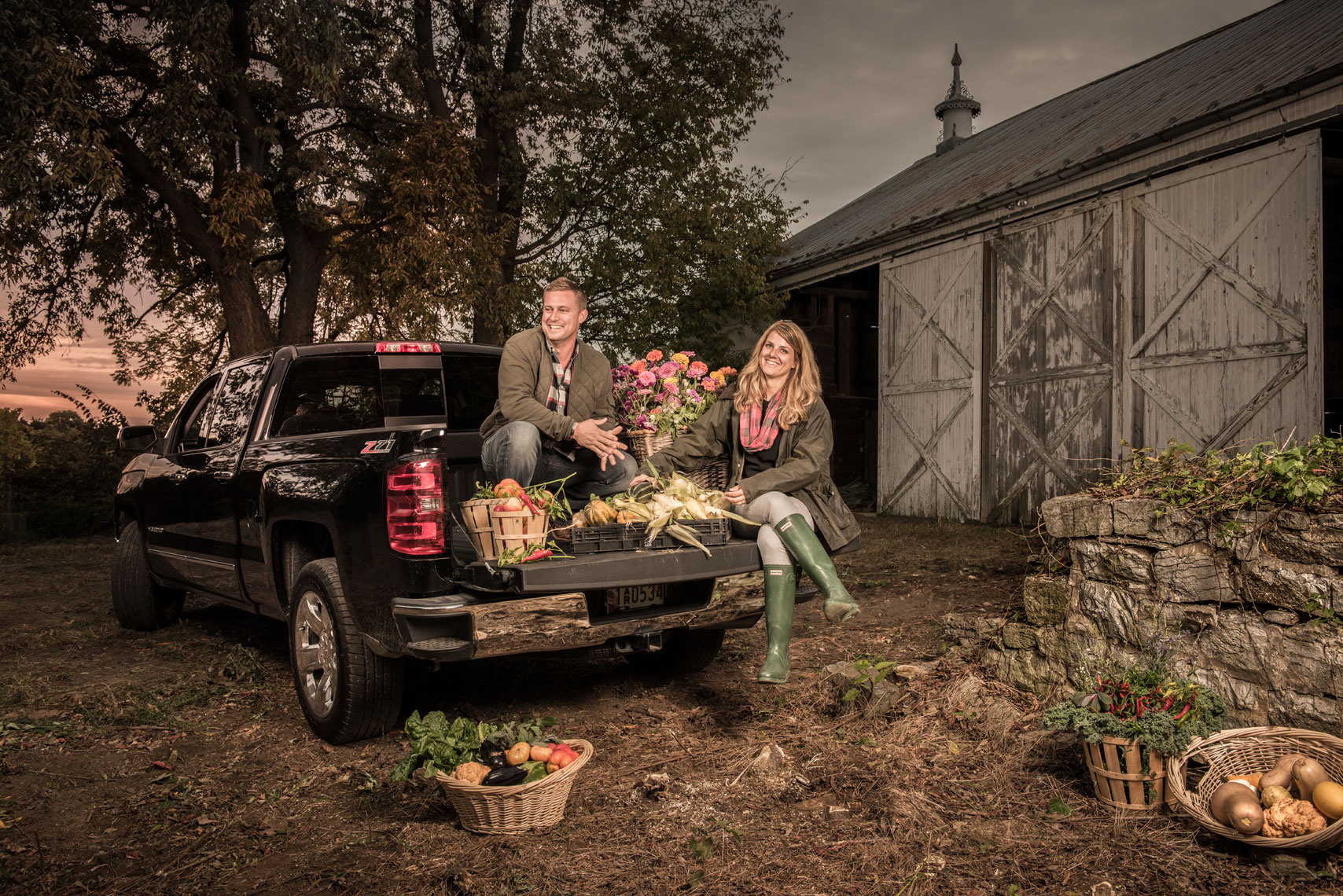 A man and a woman on the back of a pickup truck with fresh produce on a farm