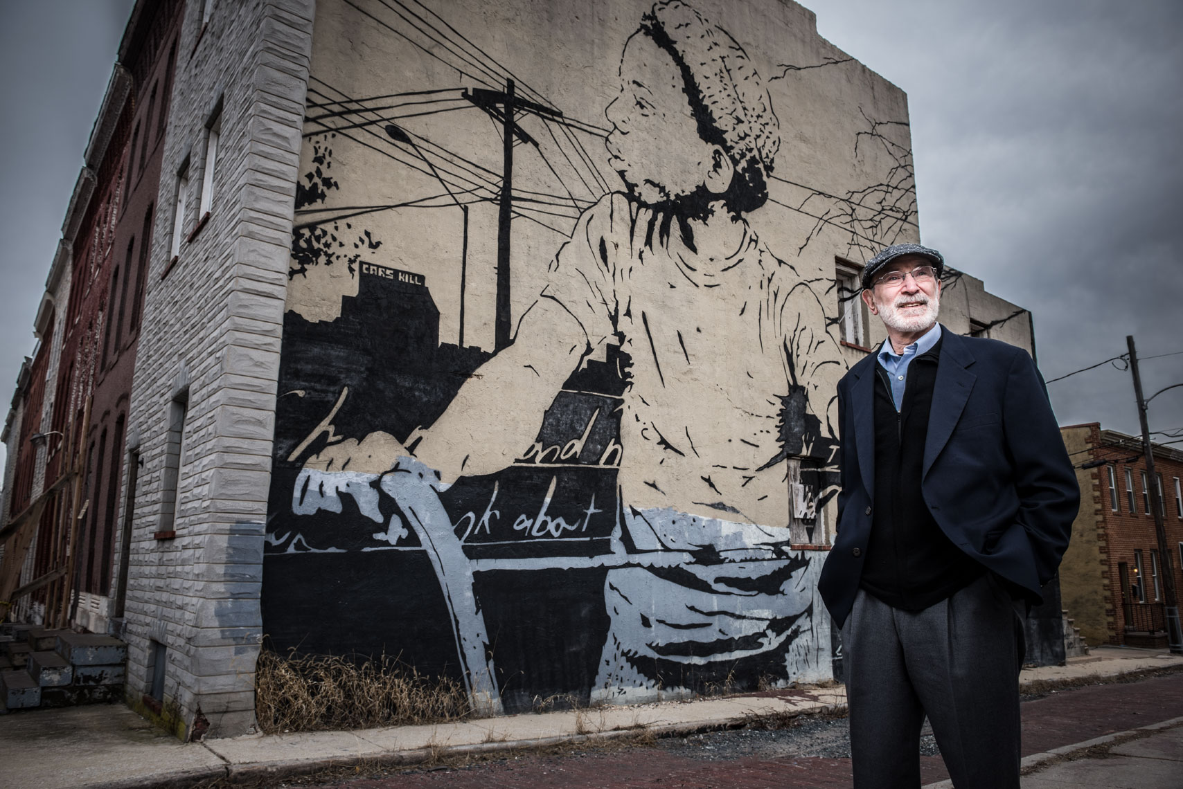 Johns Hopkins sociologist and author Dr. Karl Alexander standing in front of a mural on the streets of Baltimore.