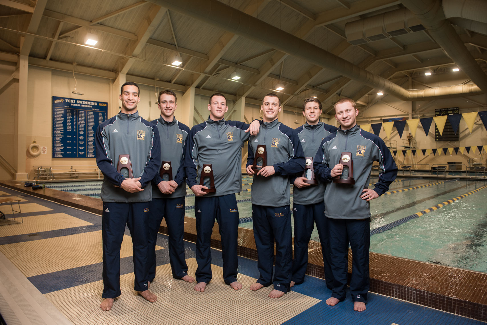 The TCNJ swim team holding their national championship plaques in front of a pool