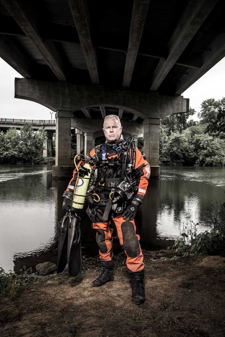 Mike Berry standing in front of water underneath a bridge in his scuba gear