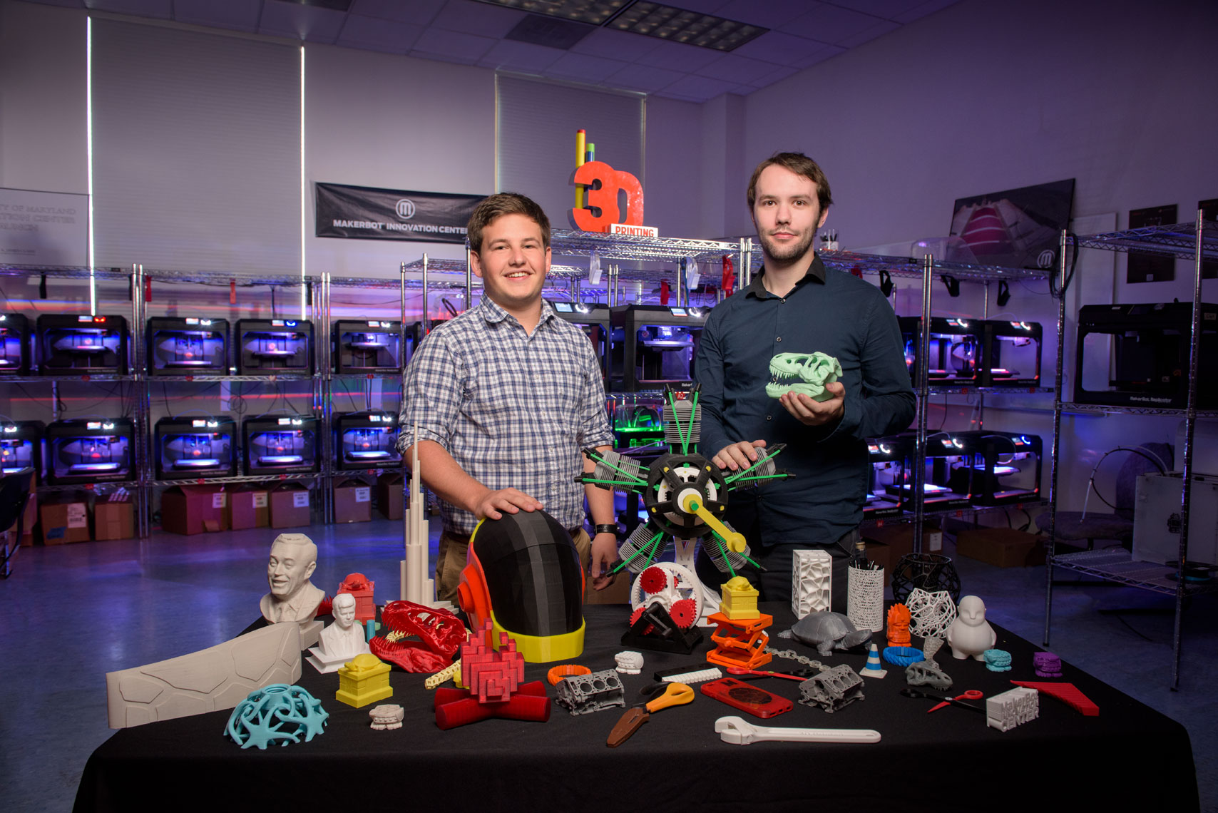 Engineering students standing with 3D printed items