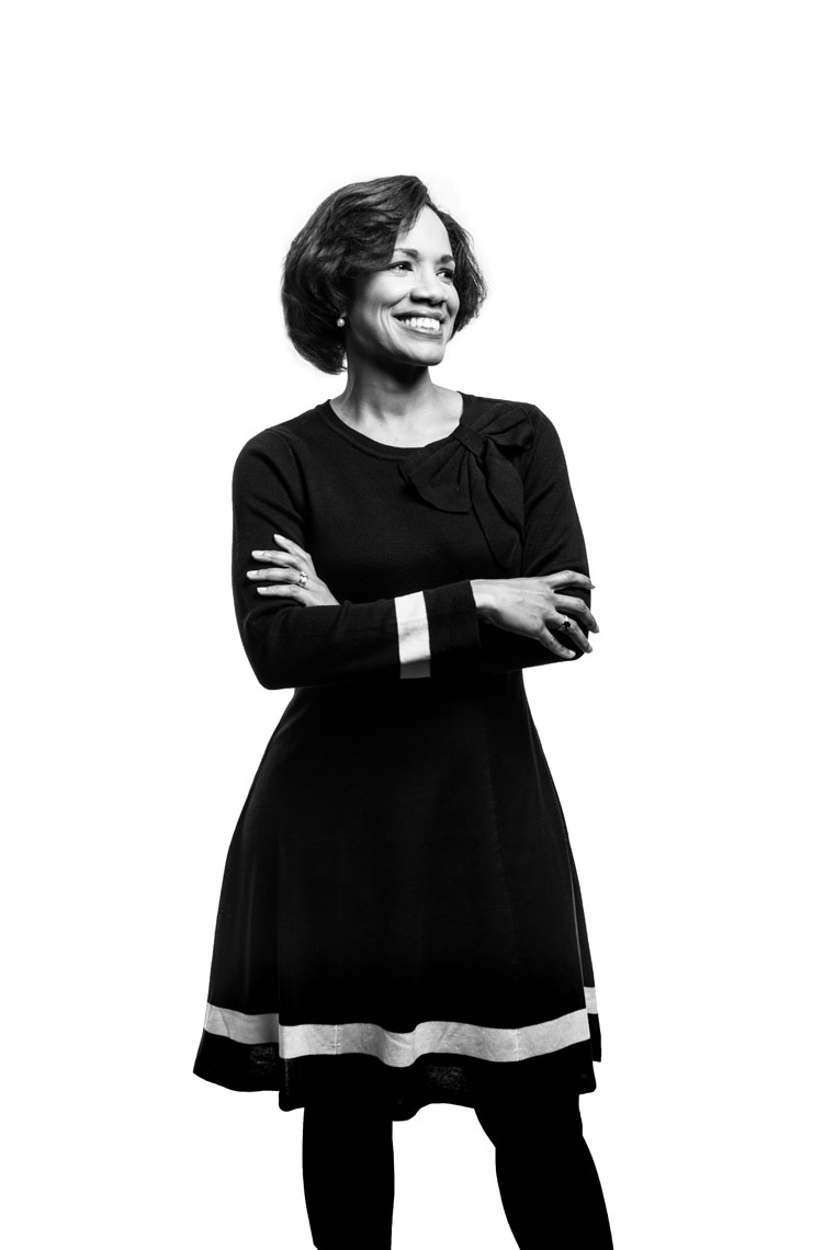 A black and white photo of a woman smiling against a white background