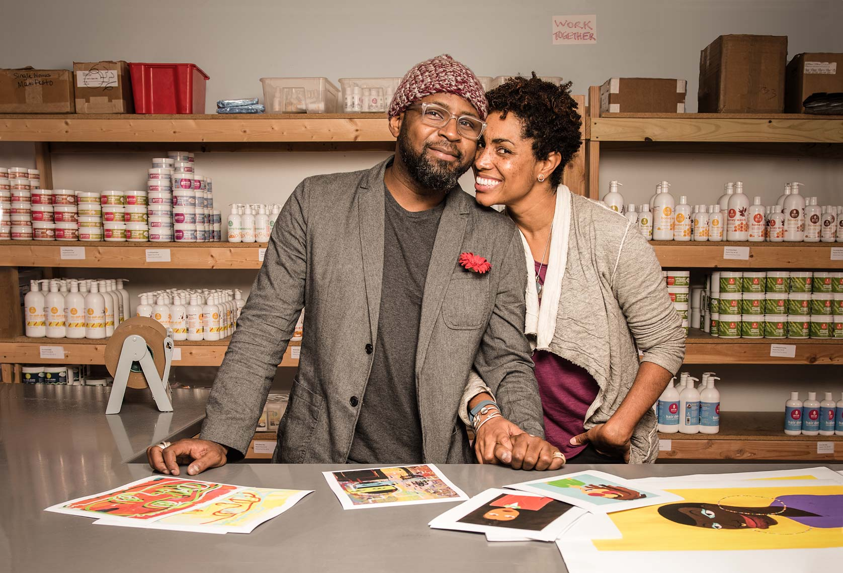 A smiling African-American couple holding hands in a workspace environment