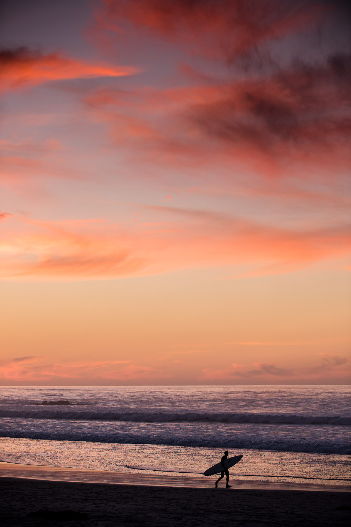 A surfer walks in silhouette under a sunset sky at Asilomar State Beach, Pacific Grove, California