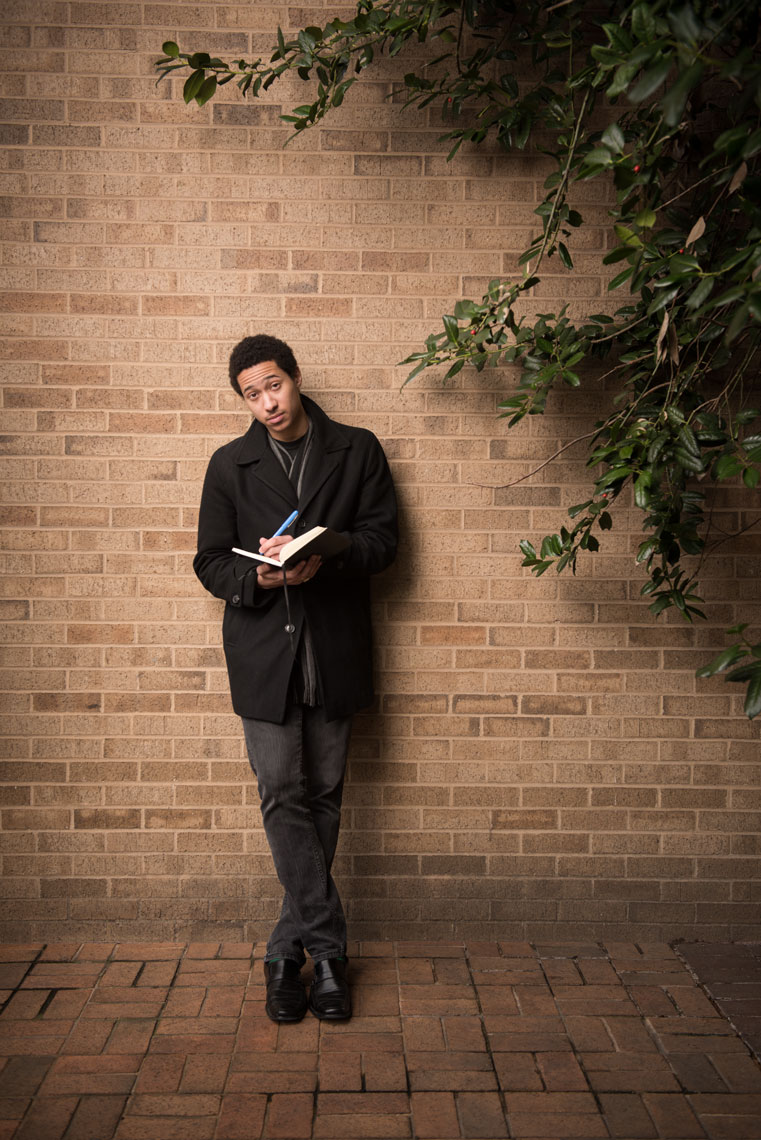 Youth Poet Laureate Derick Ebert looking up from a book and leaning against a wall