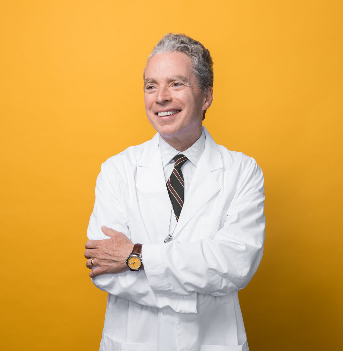 Dr. Paul Gurbel smiling in his lab coat in front of a yellow background