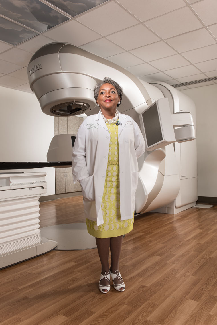 Dr. Maria Jacobs wearing a labcoat and standing in front of a radiotherapy machine