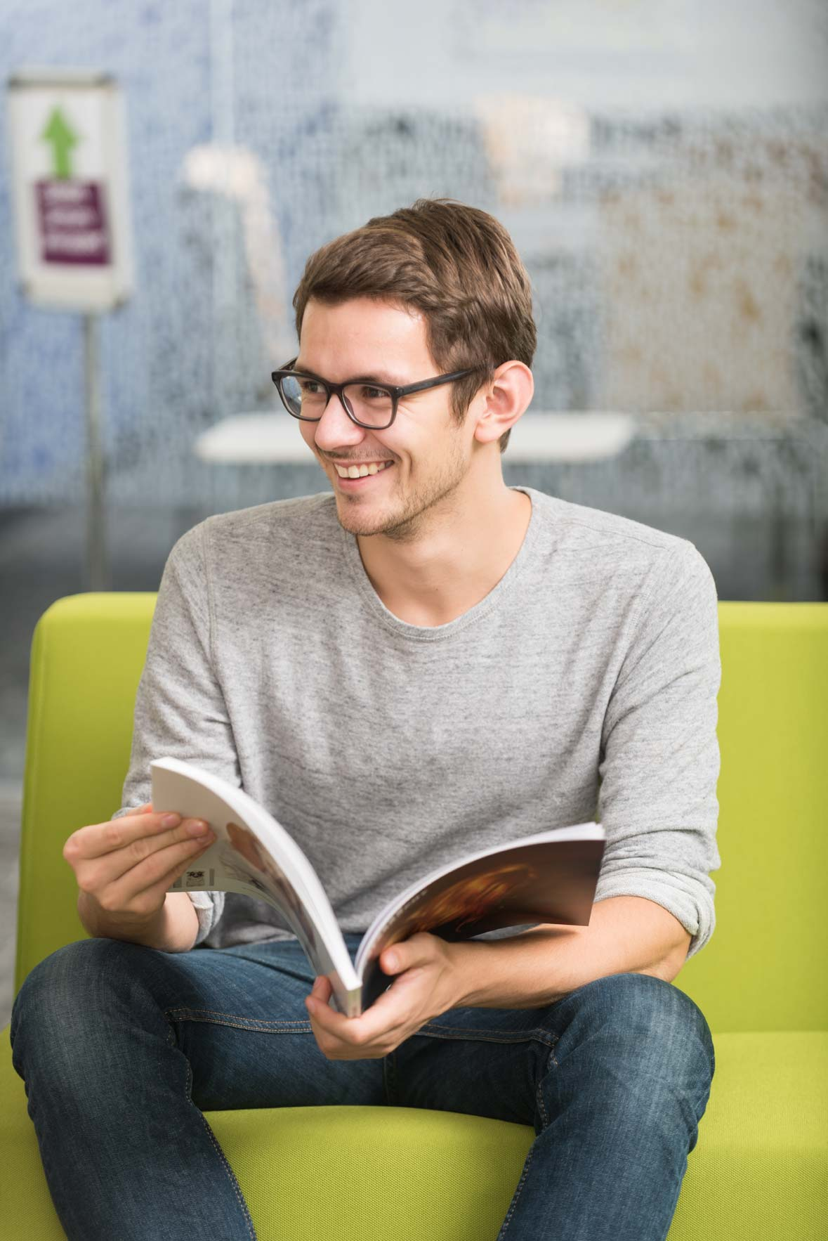 A student wearing glasses smiles while holding a magazine
