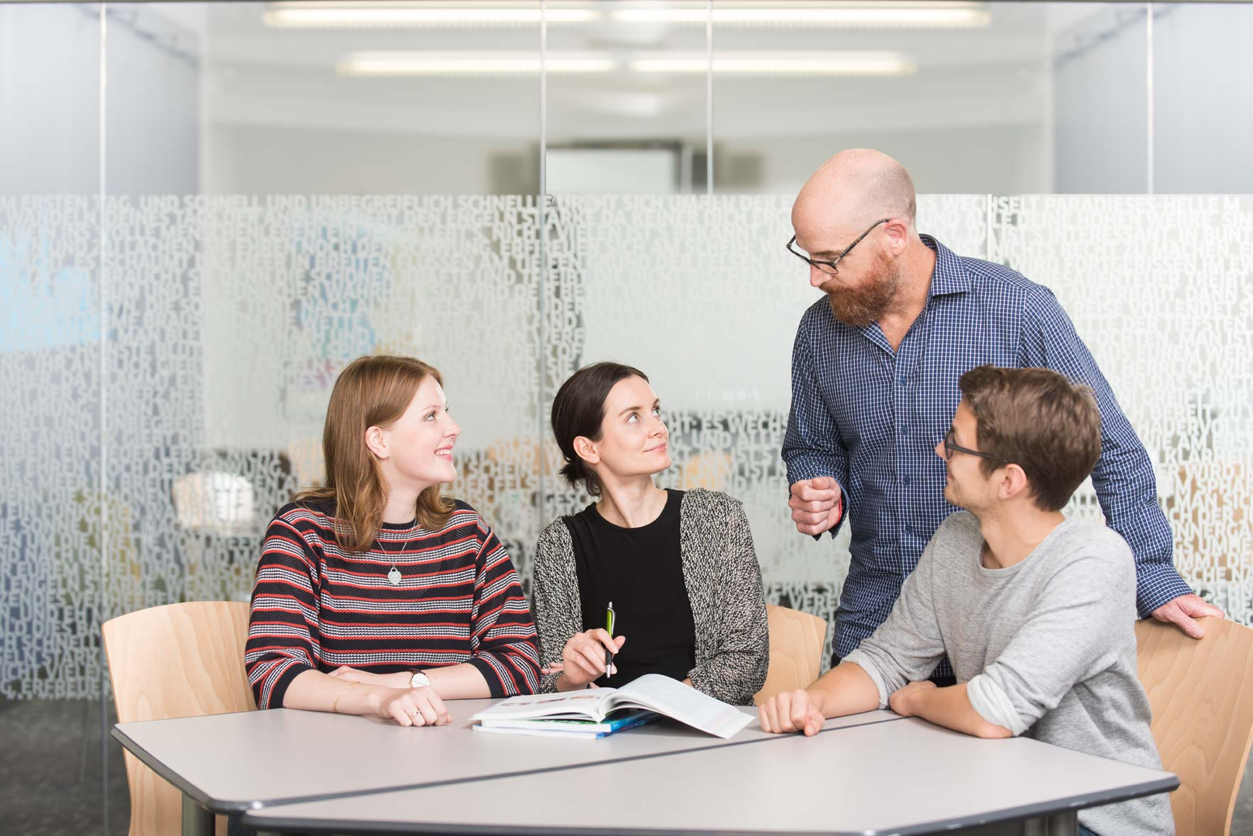 A professor talks to three students sitting at a table