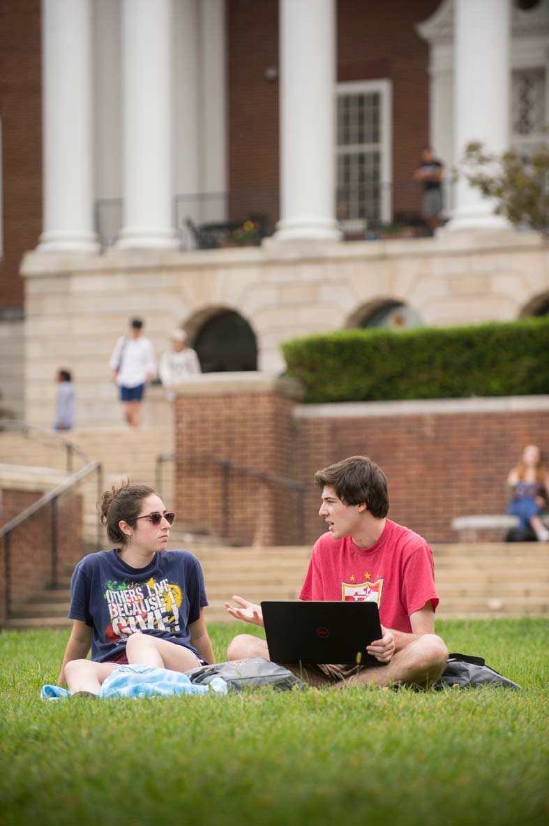 Students studying together on the lawn at a college campus