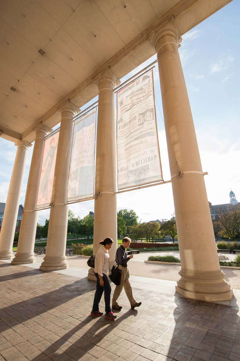 A student and a professor walk past columns on a college campus