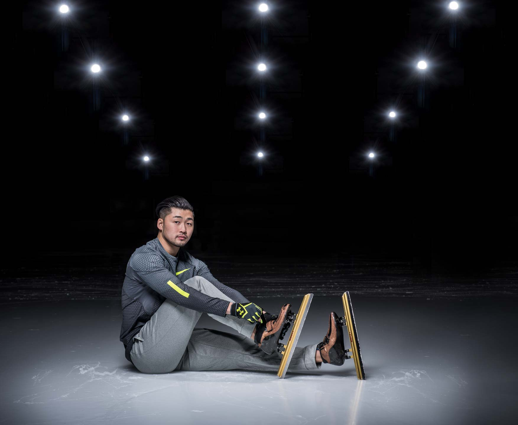 Speed skater Simon Cho adjusting his skates while seated on the ice