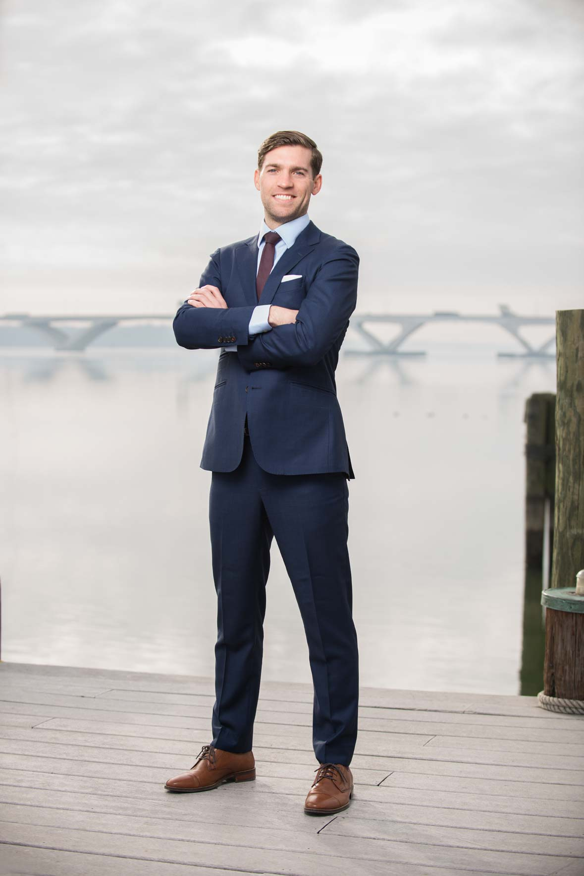 A man in a blue suit crossing his arms with a bridge in the distance