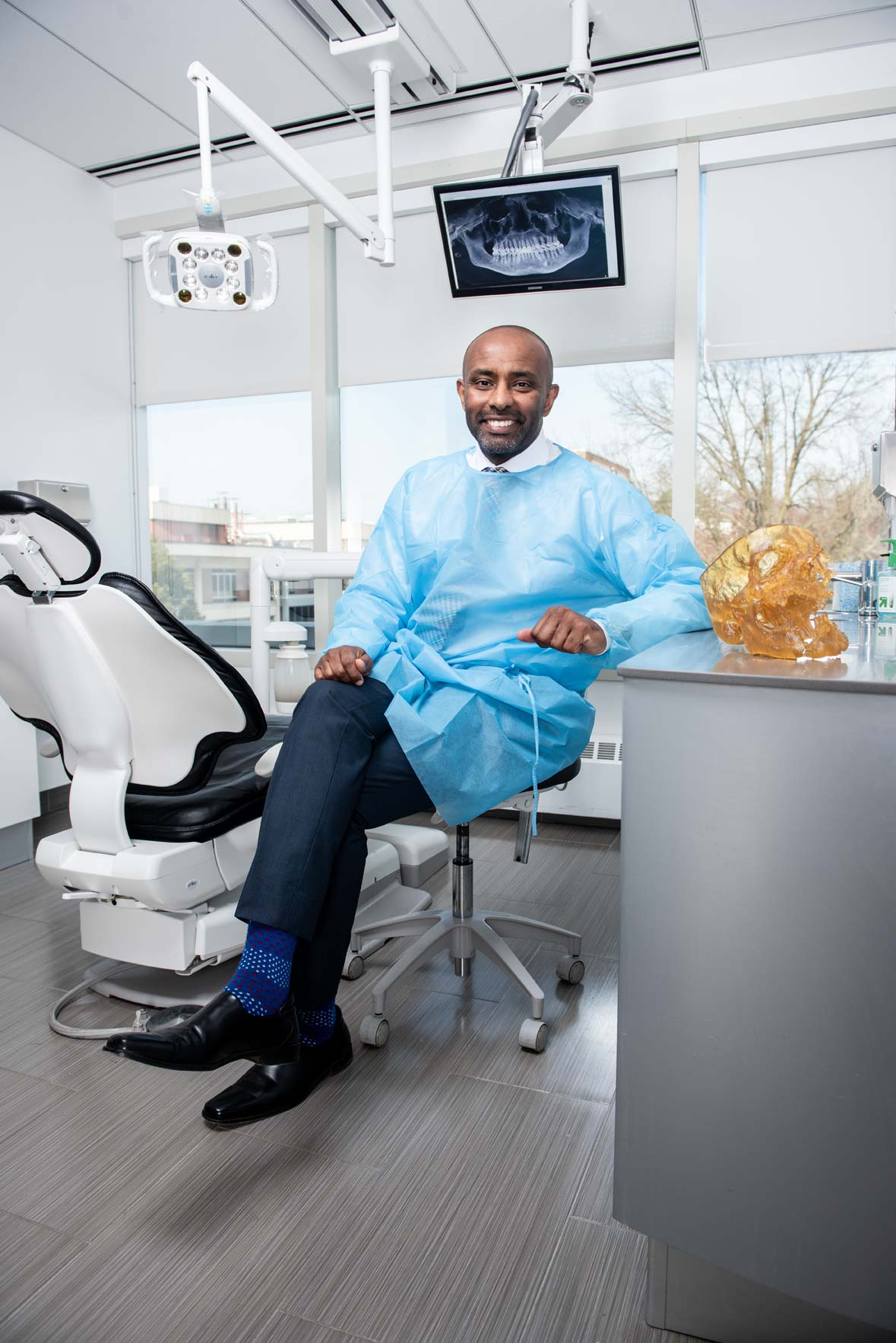 Dr. Ghassan Sinada wearing a smock and seated in front of a dental chair