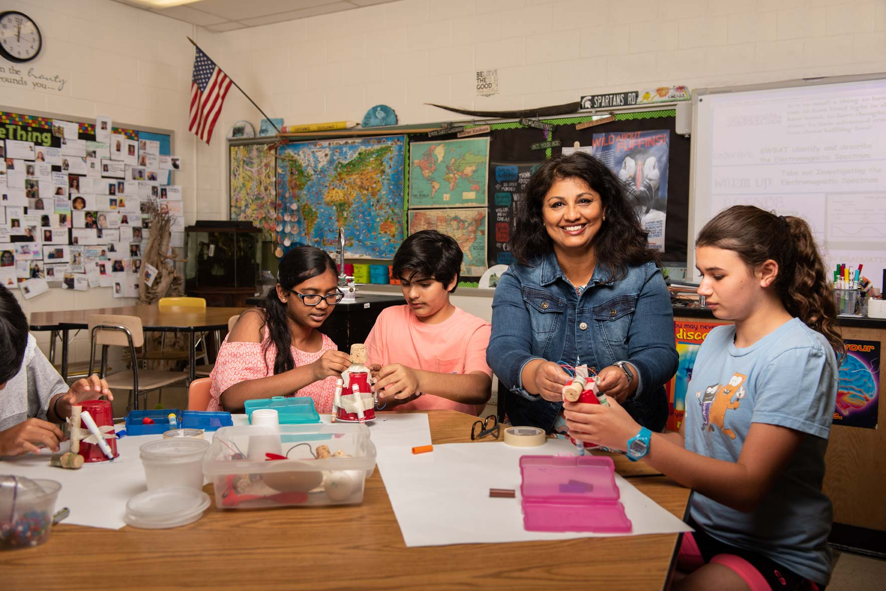 A science teacher smiles at the camera as she helps a table of students with their projects
