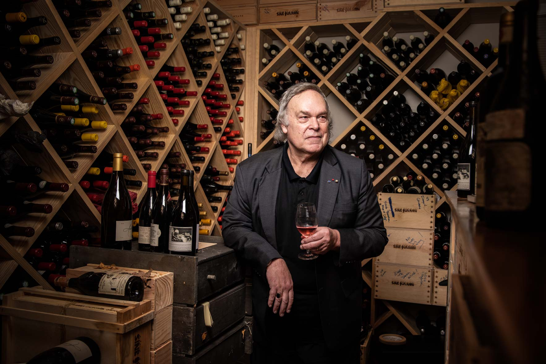 Robert Parker the Wine Advocate holding a glass of wine in his home wine cellar