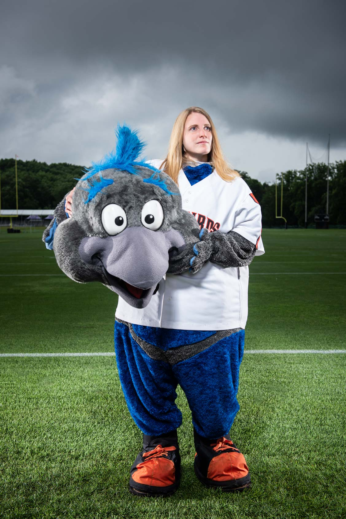 Female in a mascot costume with her mascot head in her hands