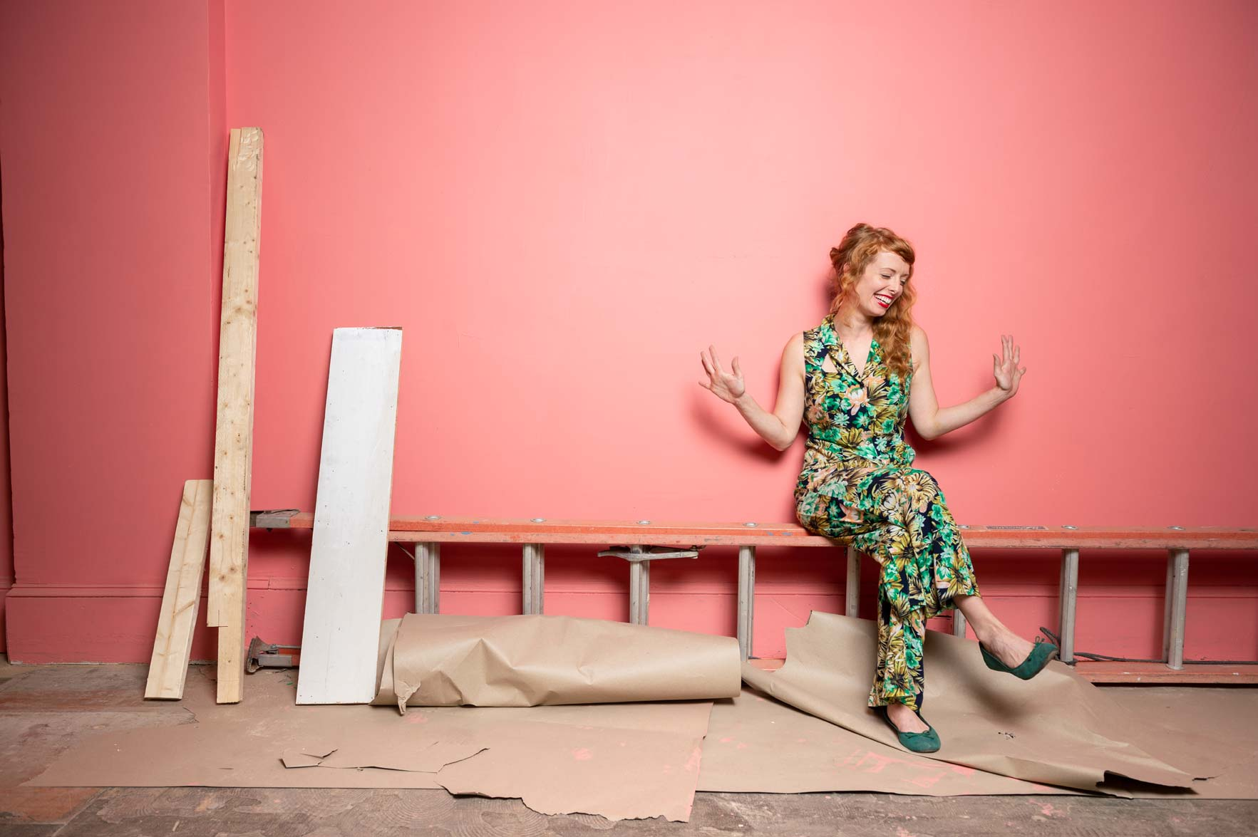 Carly Bales sitting on a ladder in front of a pink wall