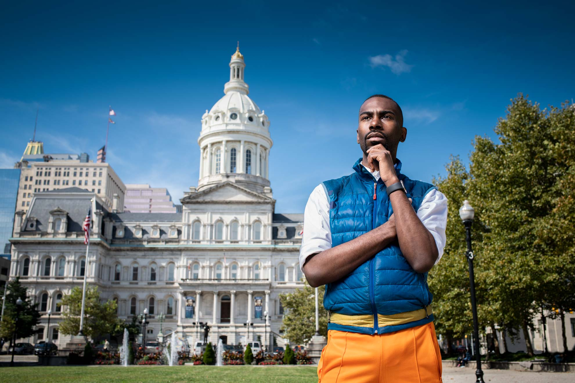 Social activist DeRay Mckesson wearing his signature blue vest in front of the Baltimore City Hall