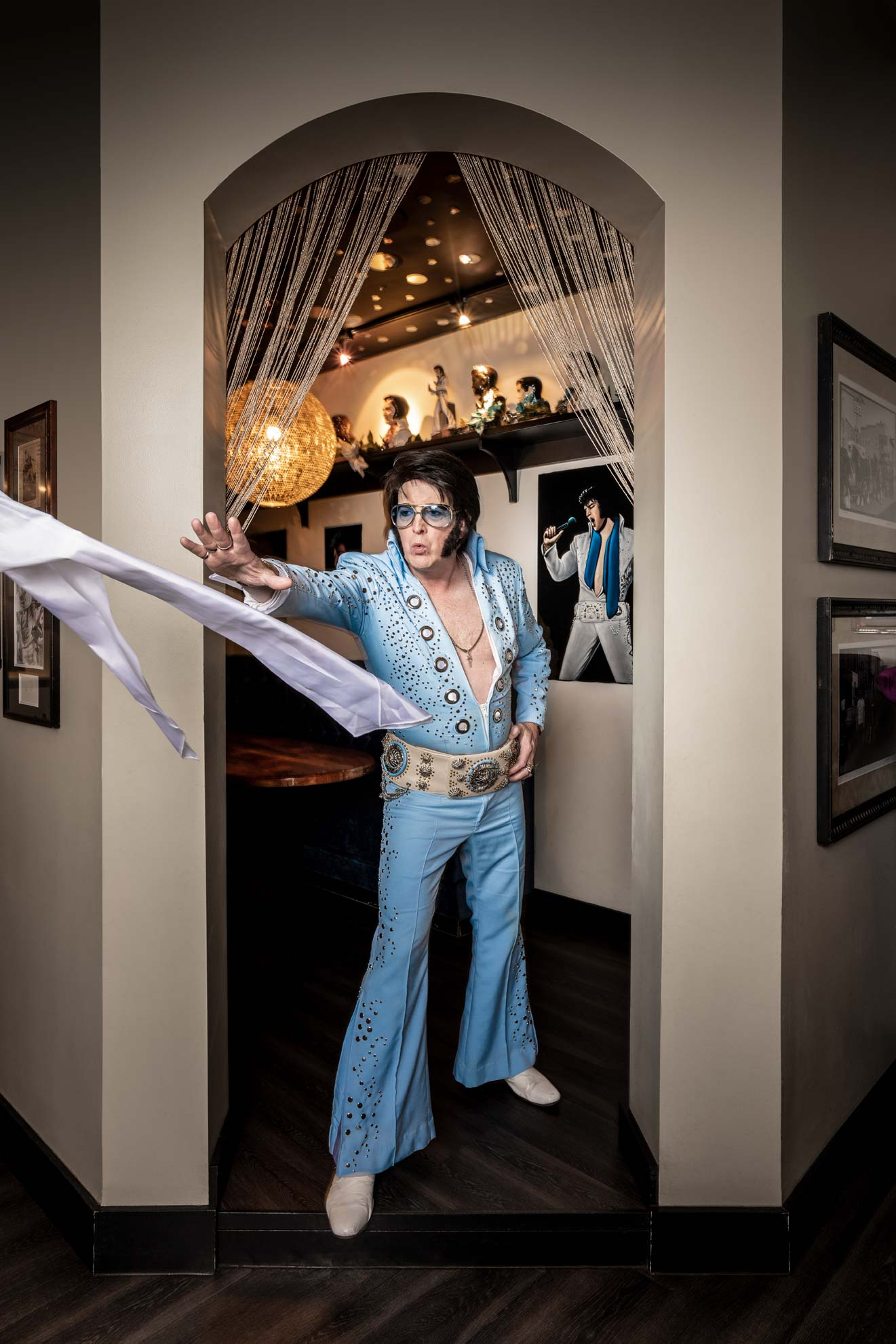 Elvis impersonator Jed Duvall standing in a doorway throwing a scarf