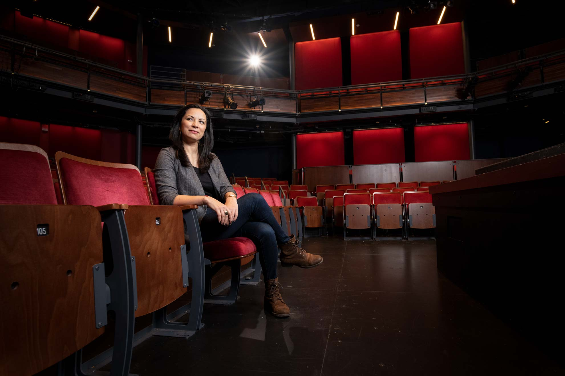 A woman seated in red velvet theater chairs