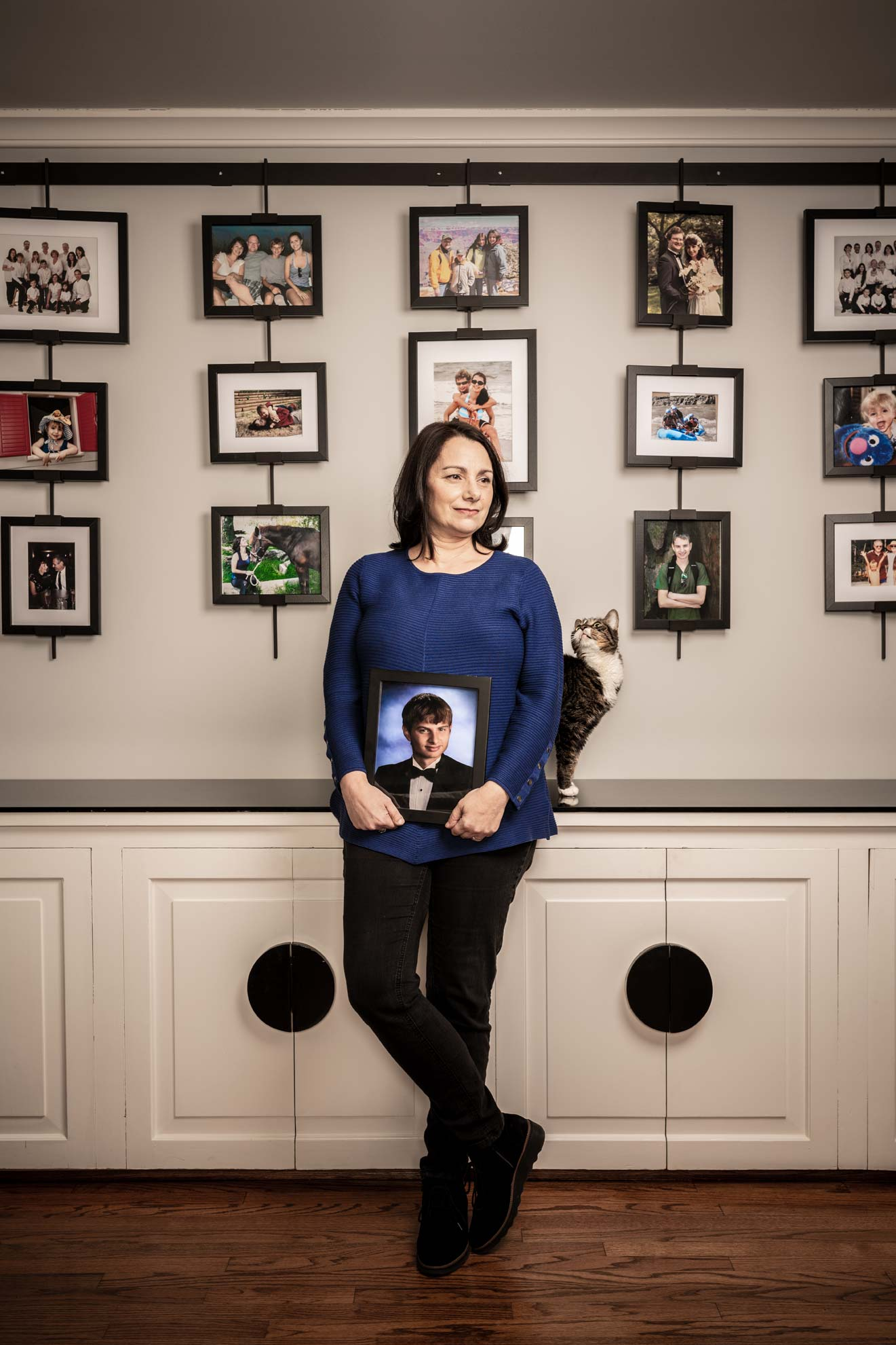 Caryn Anthony holding a portrait of her late son in front of a wall of family pictures