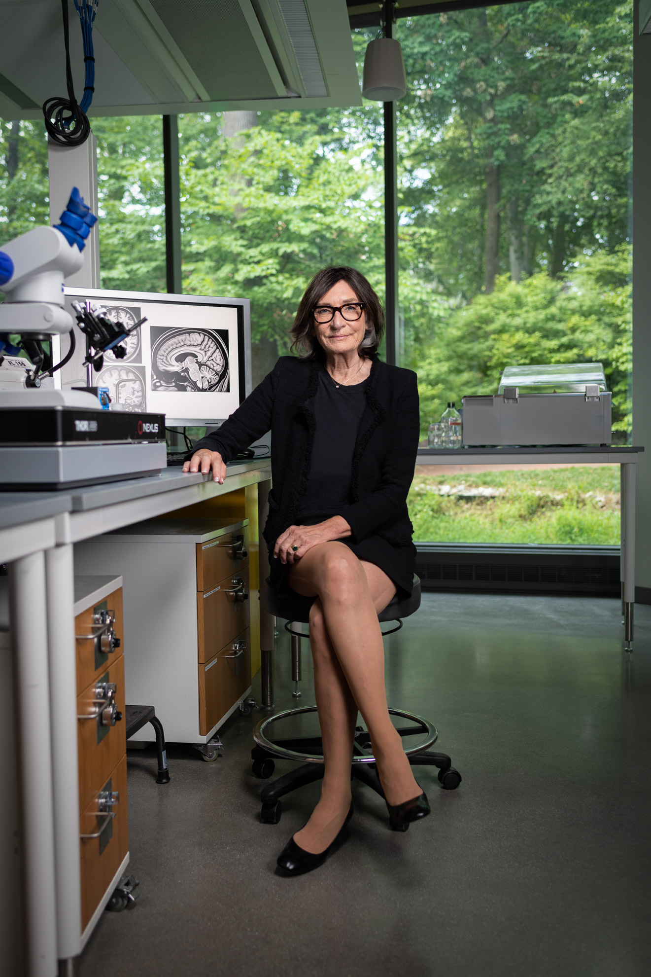 Dr. Michela Gallagher seated in a scientific lab with her legs crossed