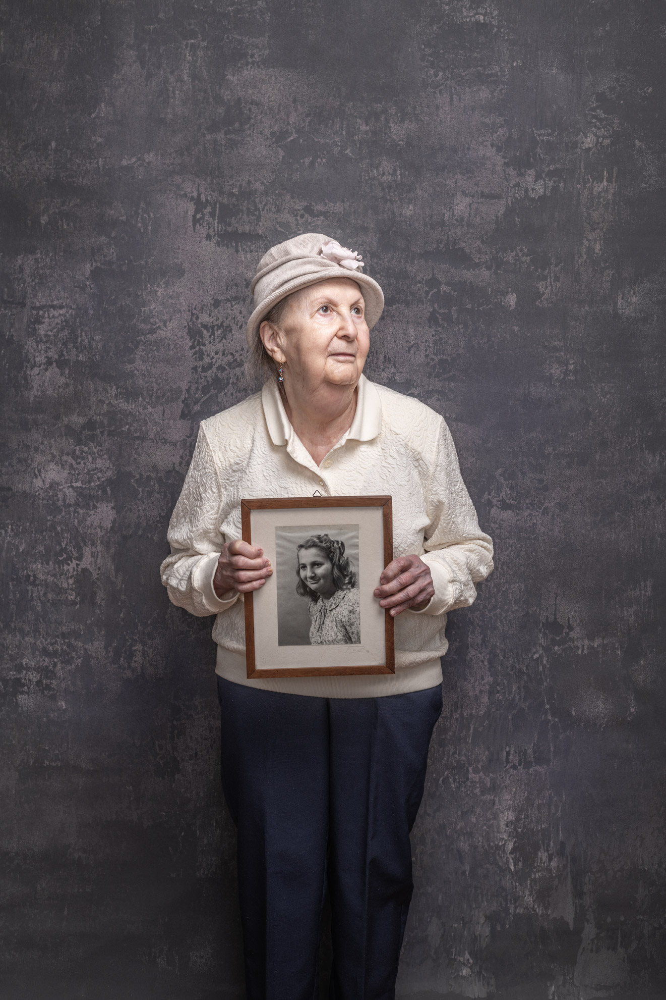 Holocaust survivor Goldie Kalib holding a portrait of herself as a young girl