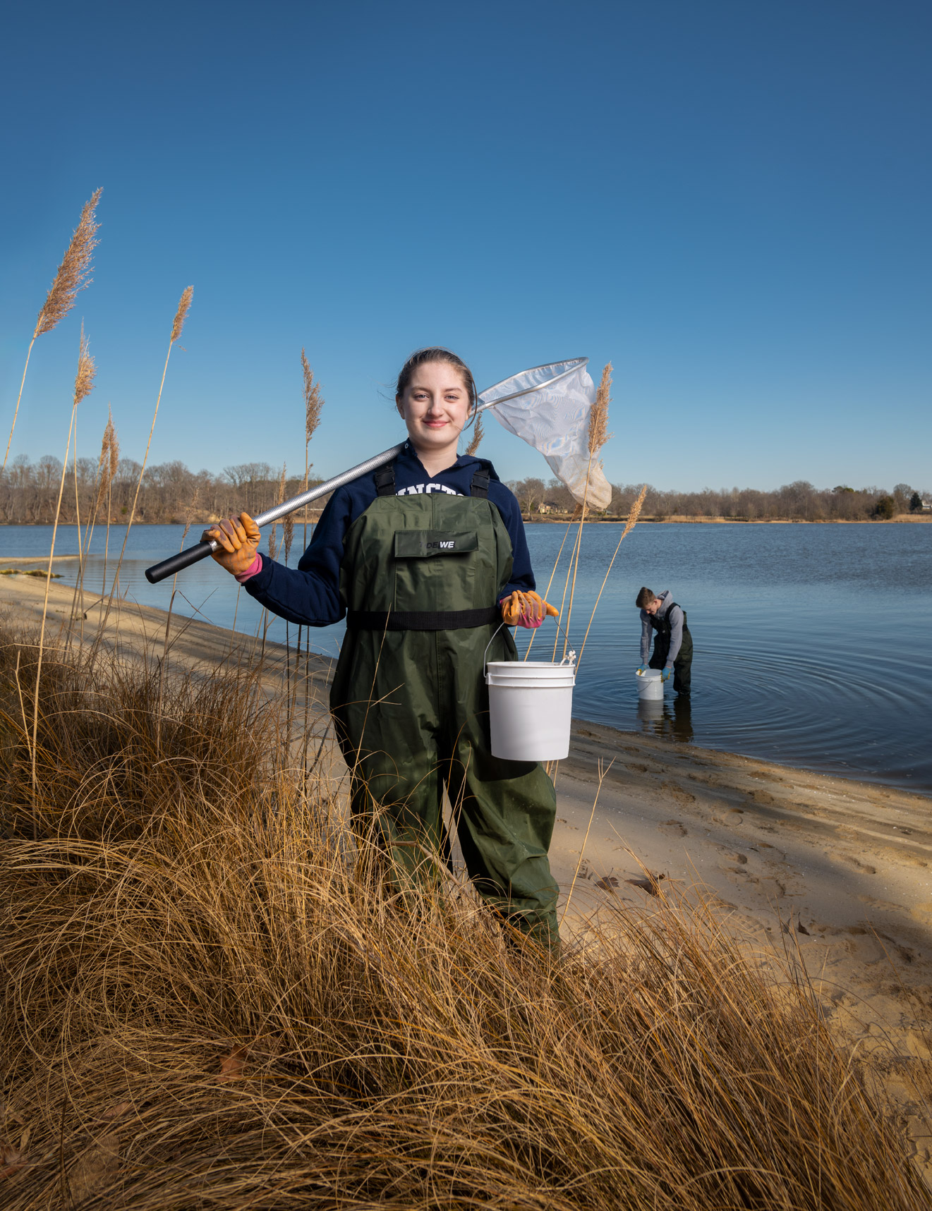 A high school student stands on the shoreline wearing waders and holding a net and a bucket