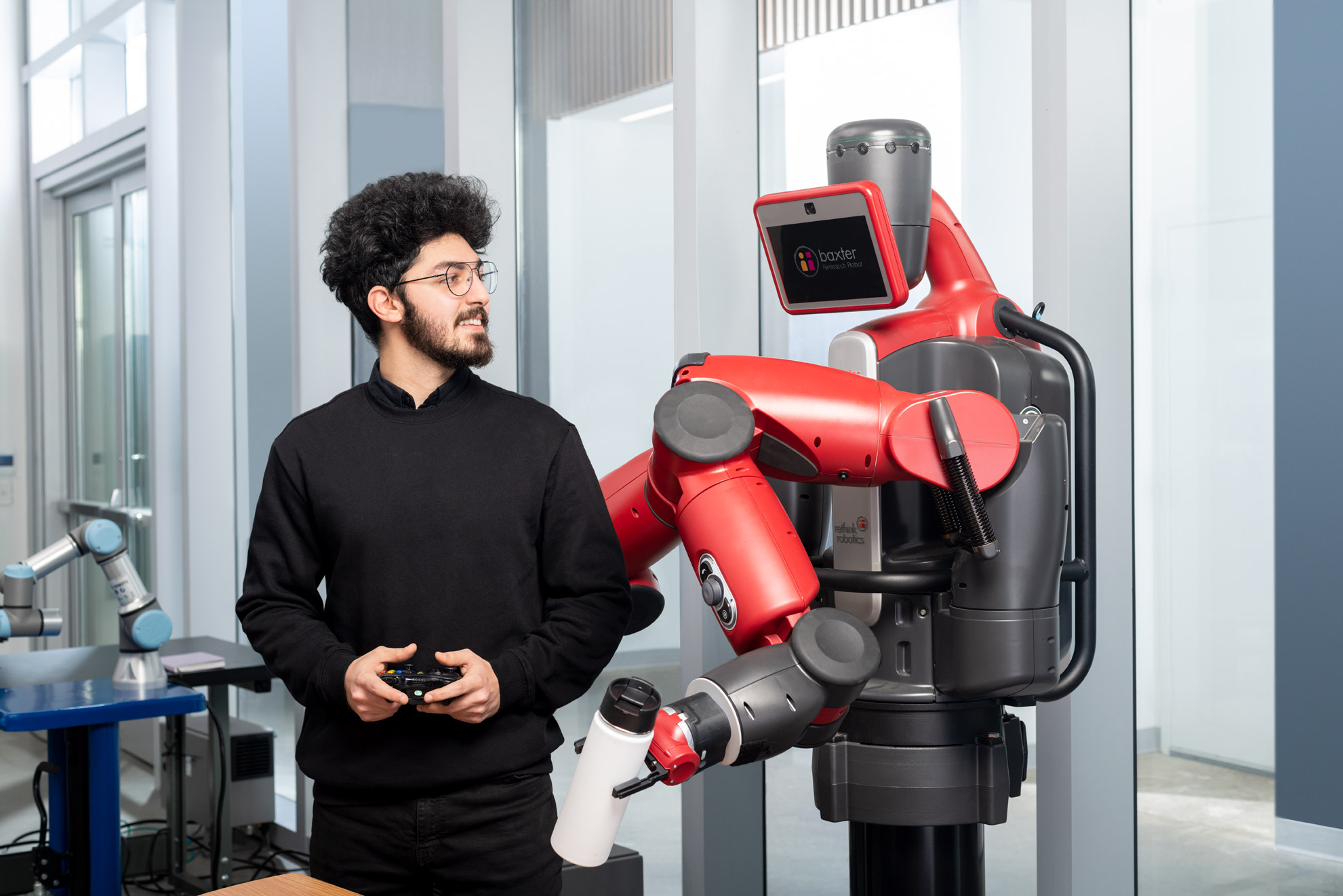 An engineering  student stands with Baxter the robot in a lab