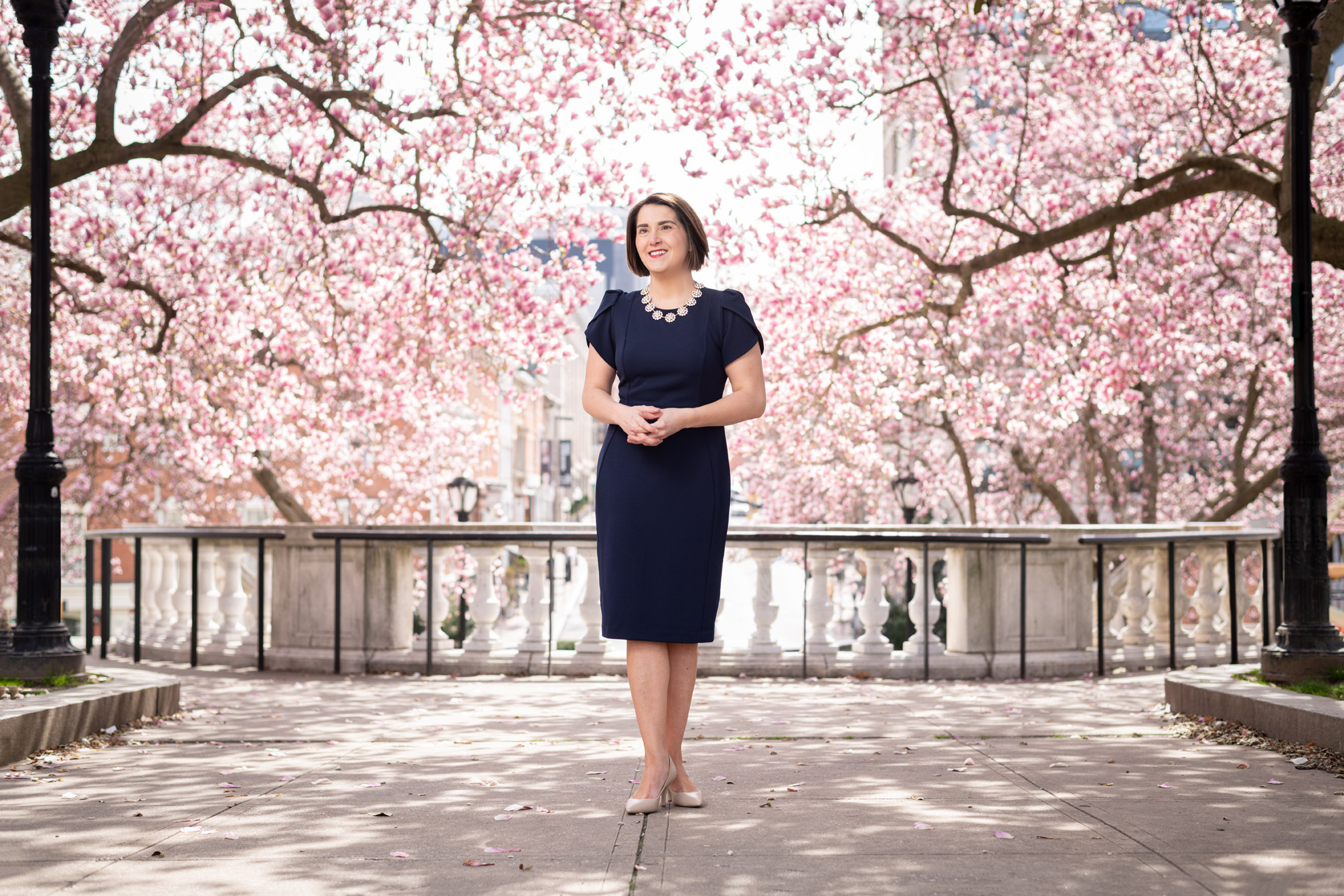 Soprano Chelsea Buyalos standing in front of pink flowering trees