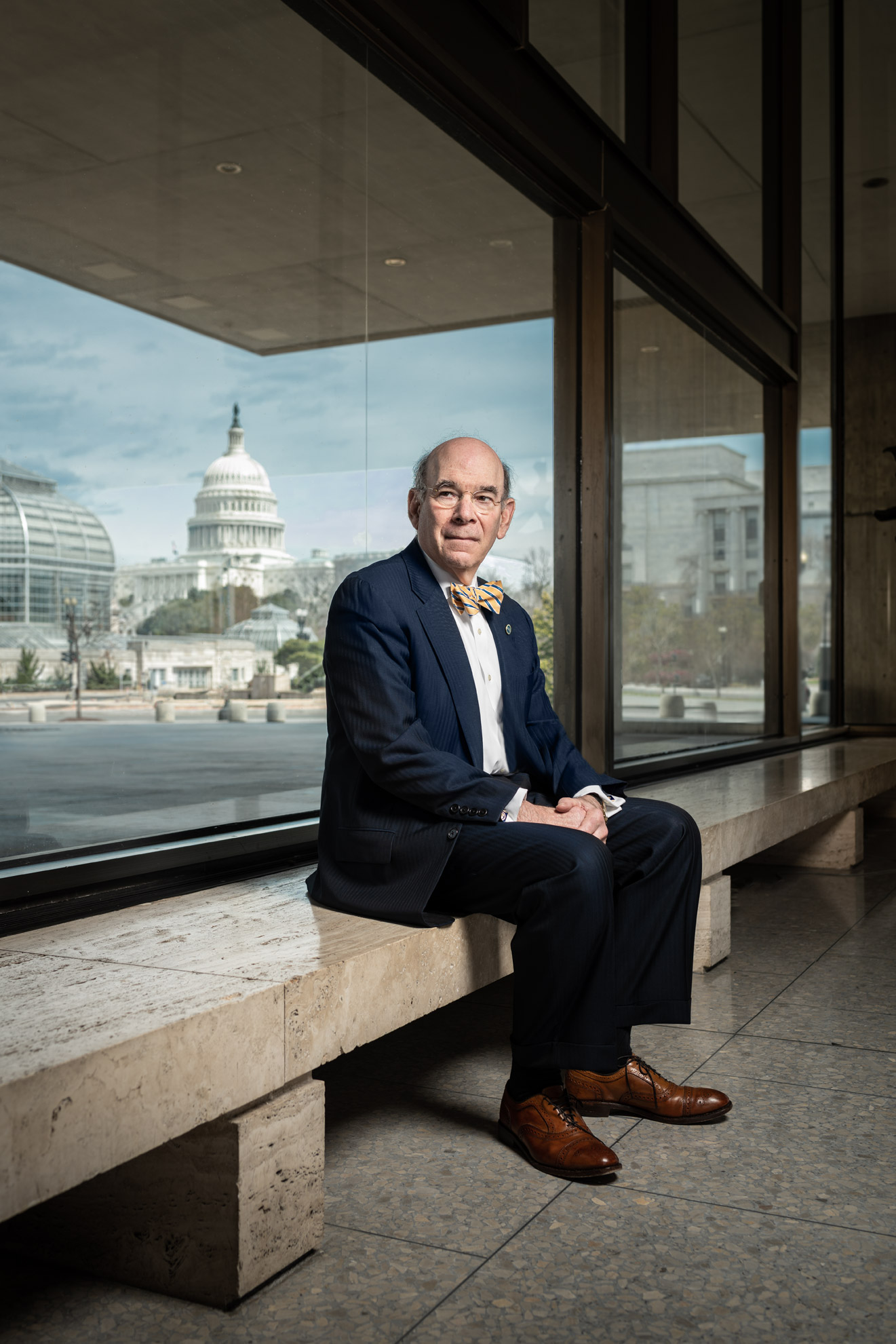 Robert Charrow, General Counsel, seated on a bench in the HHS lobby