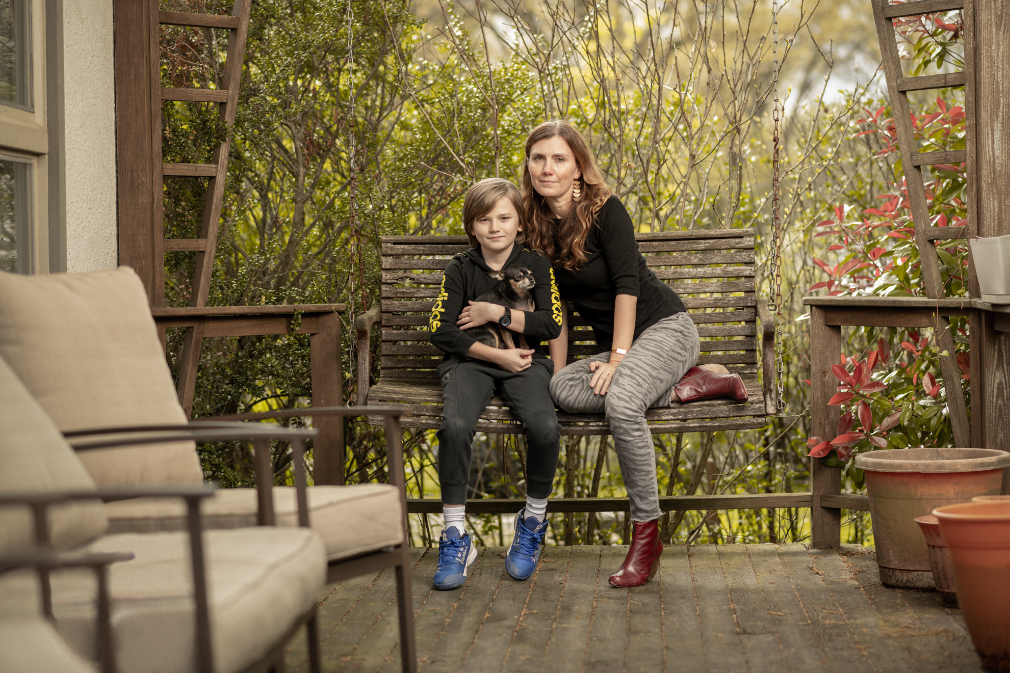 COVID-19 survivor Cara Ober and her son seated on a porch swing at her home