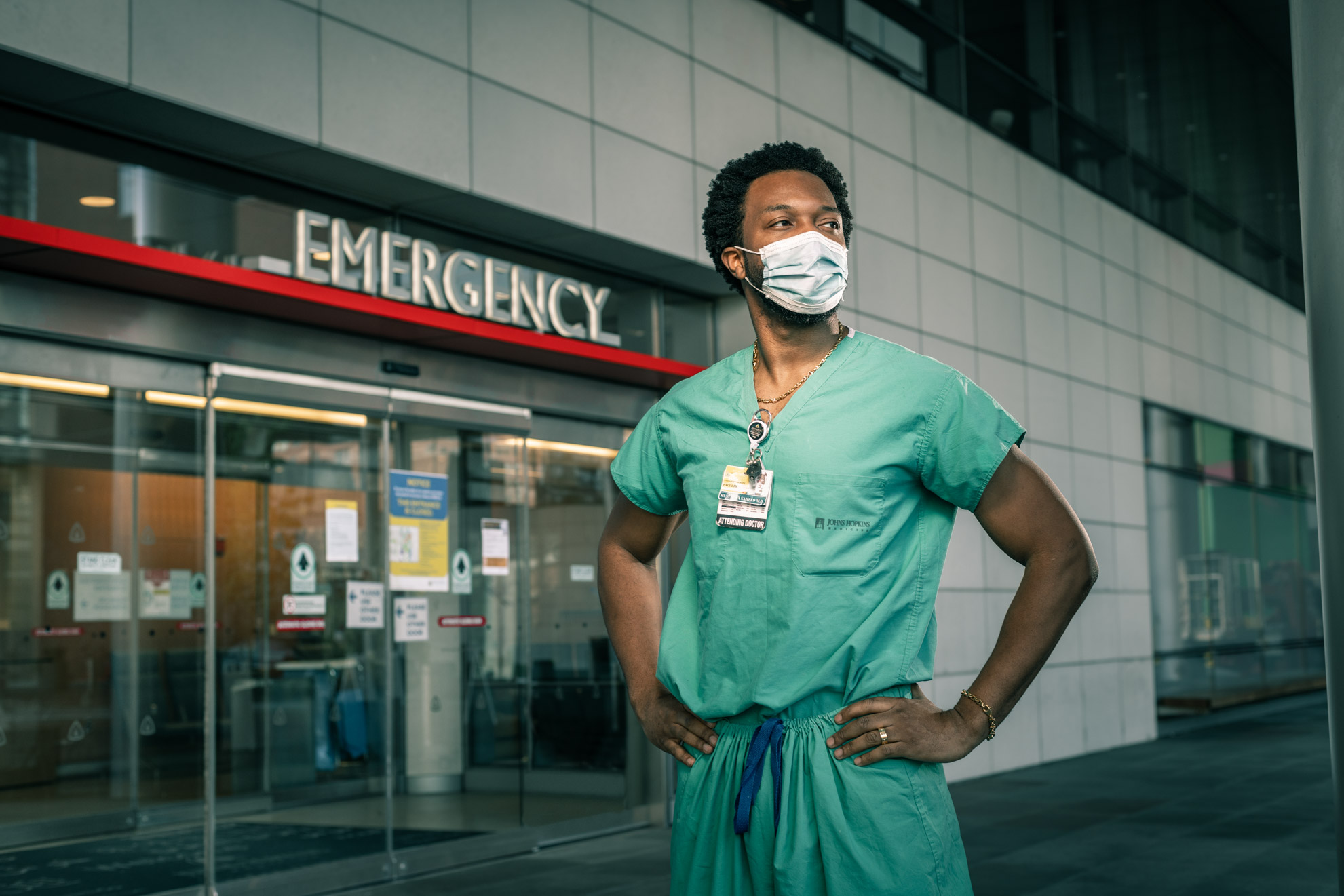 Dr. Mustapha Oladapo Saheed wearing scrubs and his COVID mask in front of the emergency entrance