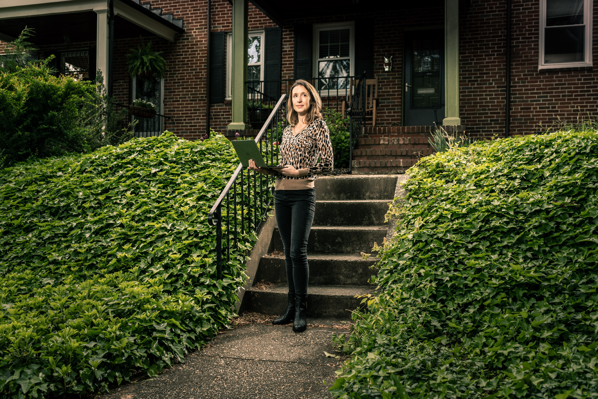 Dr. Lauren Gardner standing with a laptop outside of her Baltimore home