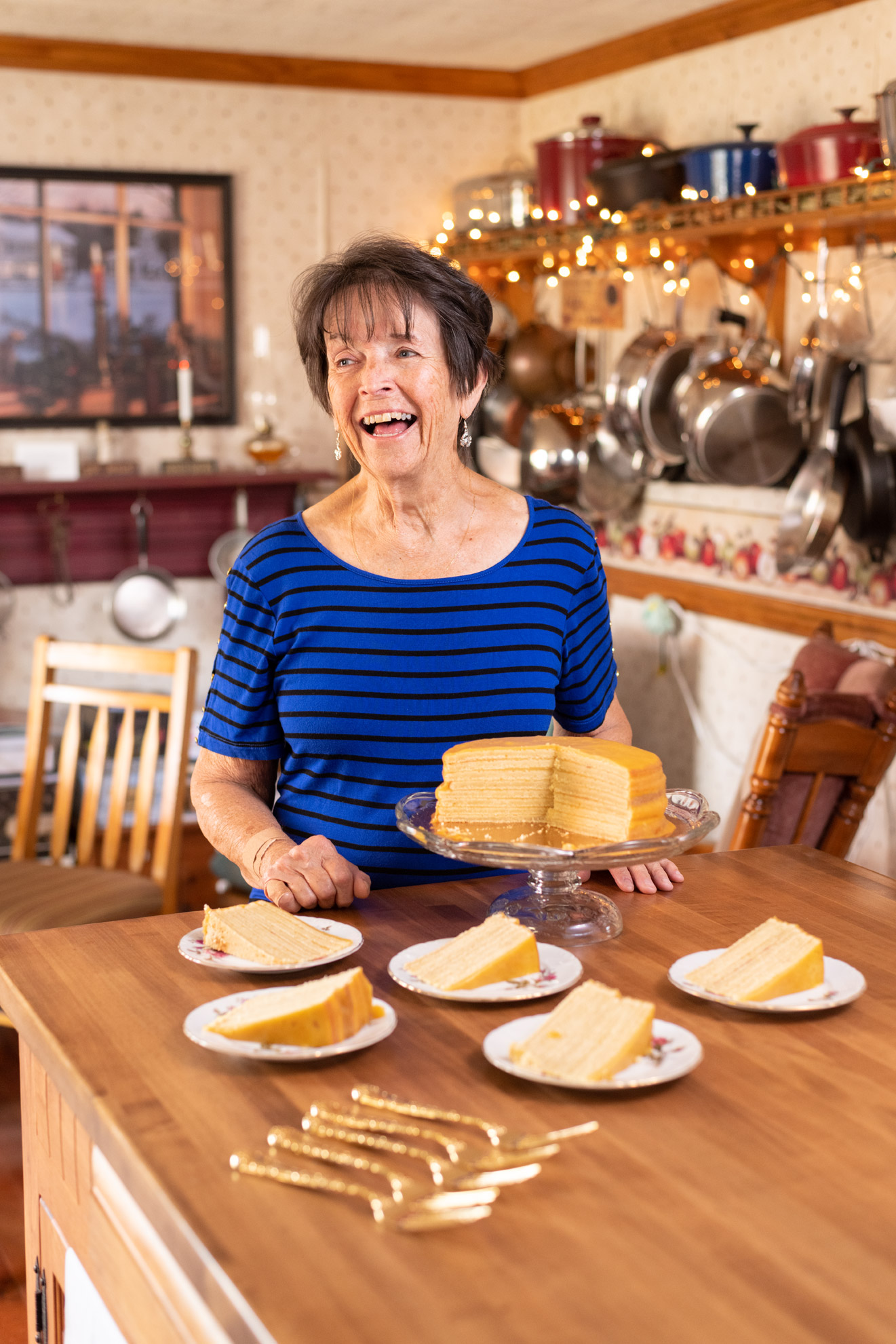 A woman laughing with a Smith Island cake