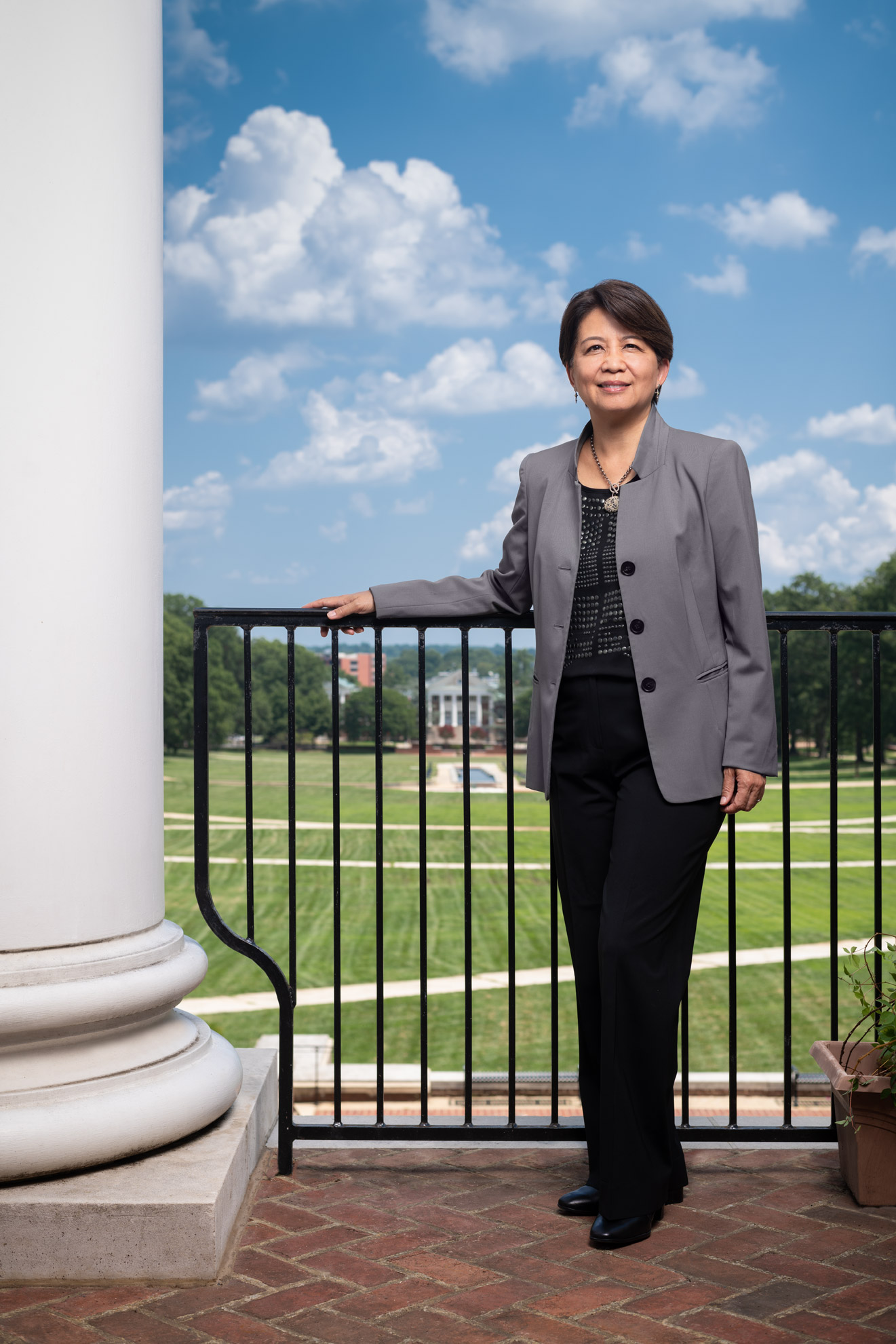 University of Maryland Libraries Dean Adriene Lim stands with the campus behind her
