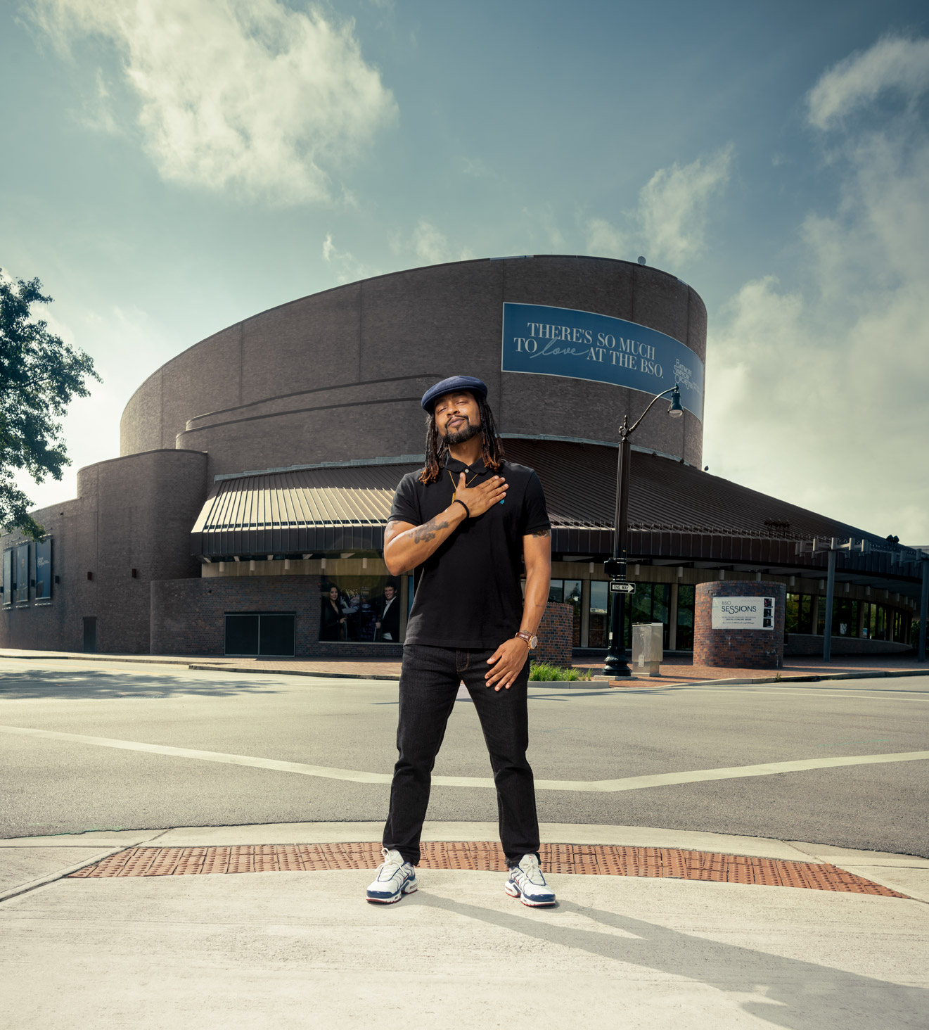 Wordsmith the rapper standing in front of the Meyerhoff Symphony Hall with his hand on his chest